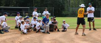 Young baseball players gathered in the infield with a coach and older players.