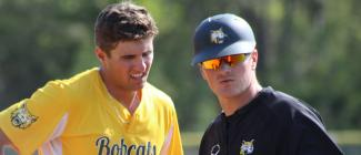Baseball coach talks with player.
