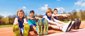 pre-teen children stretching, while sitting on outdoor running track with treelined blue sky background