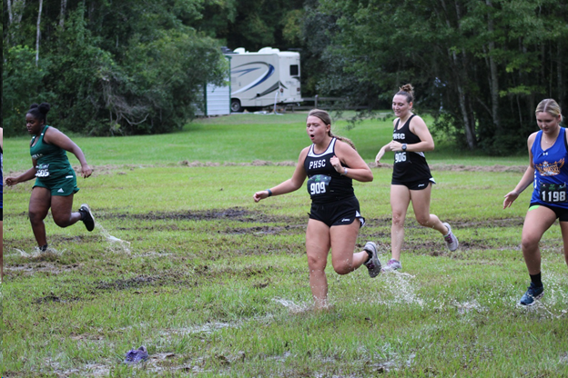 Runners race through wet and muddy grass track.